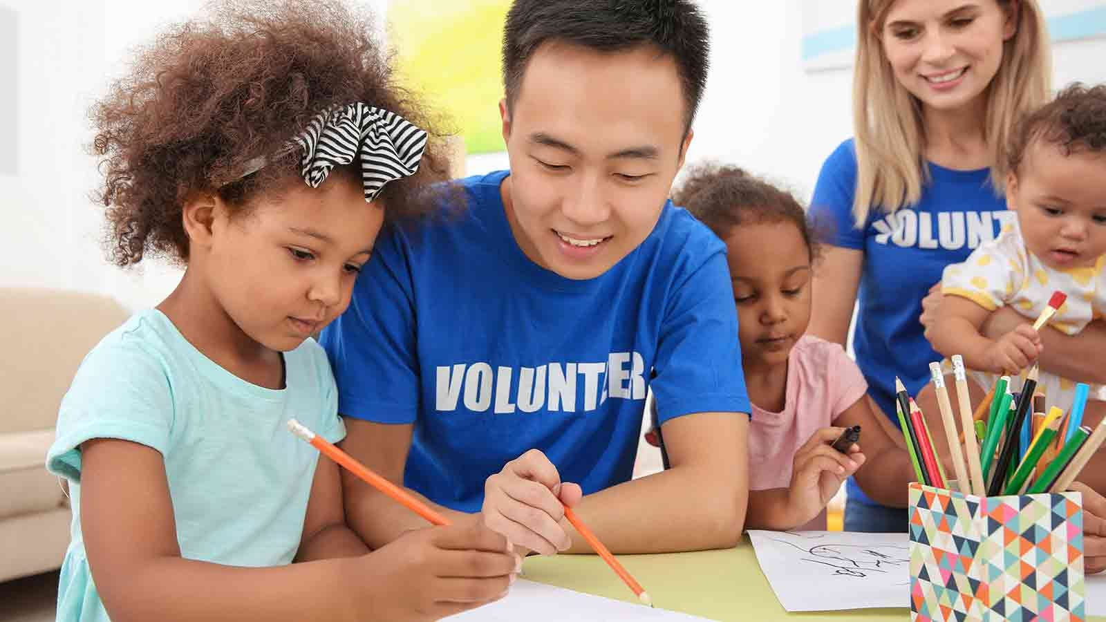 volunteers helping young children draw and work on homework