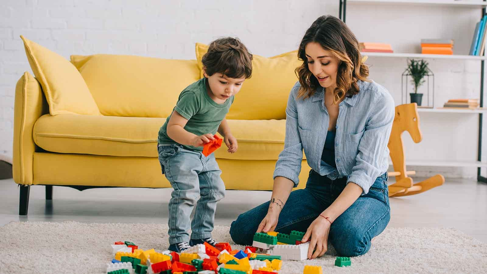Mother playing with her son on the floor with building blocks