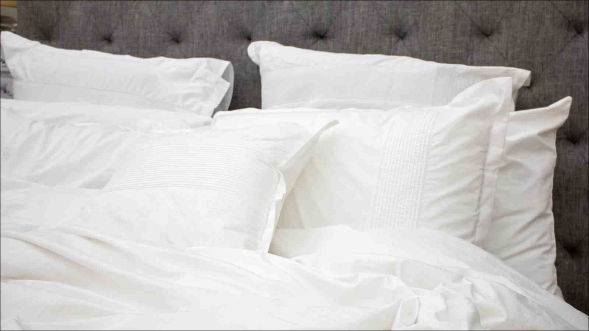 Bed with white sheets, pillows and blanket