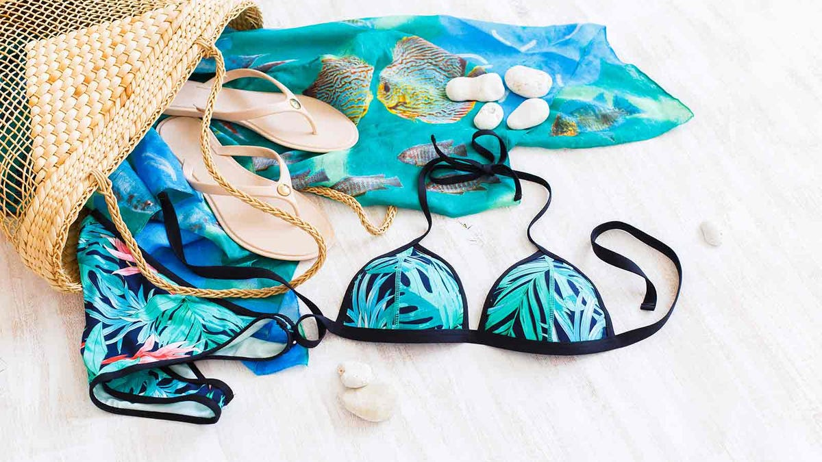 Beach bag with swimsuit, flip flops, and a pretty sarong wrap on a light background
