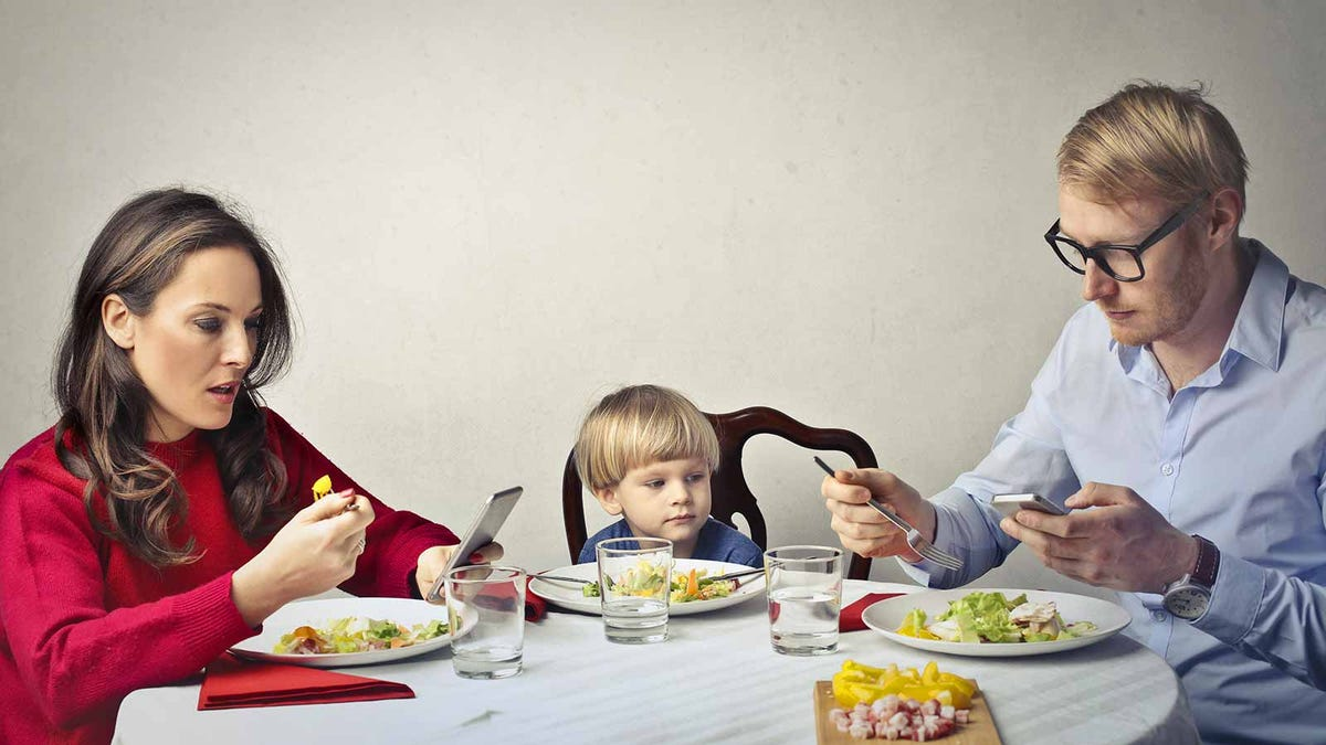 Distracted parents looking at their phones during dinner as their child looks on.
