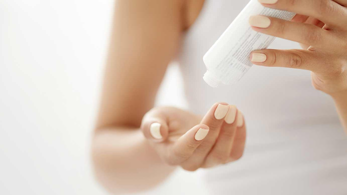 A woman's hands dispensing topical cream from a bottle