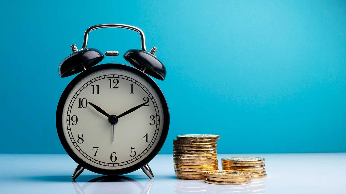 a clock and a pile of coins against a blue background