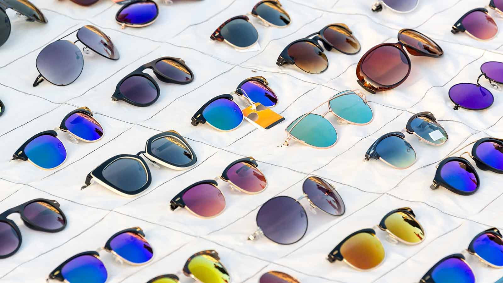 Dozens of sunglasses laid out on a store table