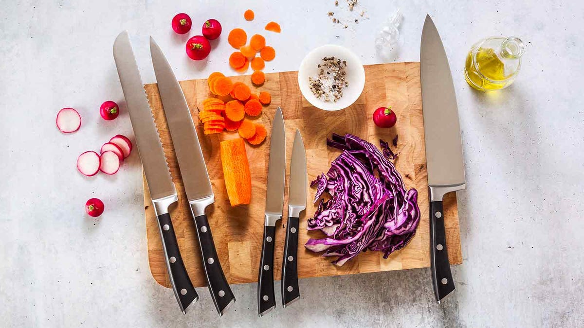 Set of knives on a wooden cutting board with some vegetables.