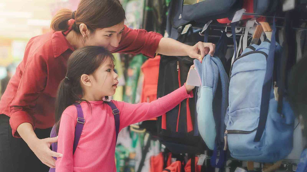 Young mother shopping school supplies with her early elementary age daughter