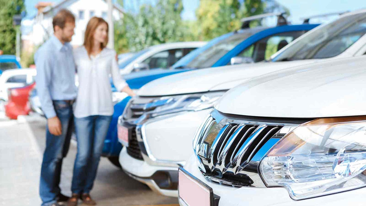 Man and woman looking at cars at a car lot.