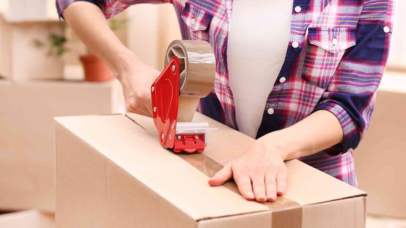 Woman's hands taping up a box with a tape gun.