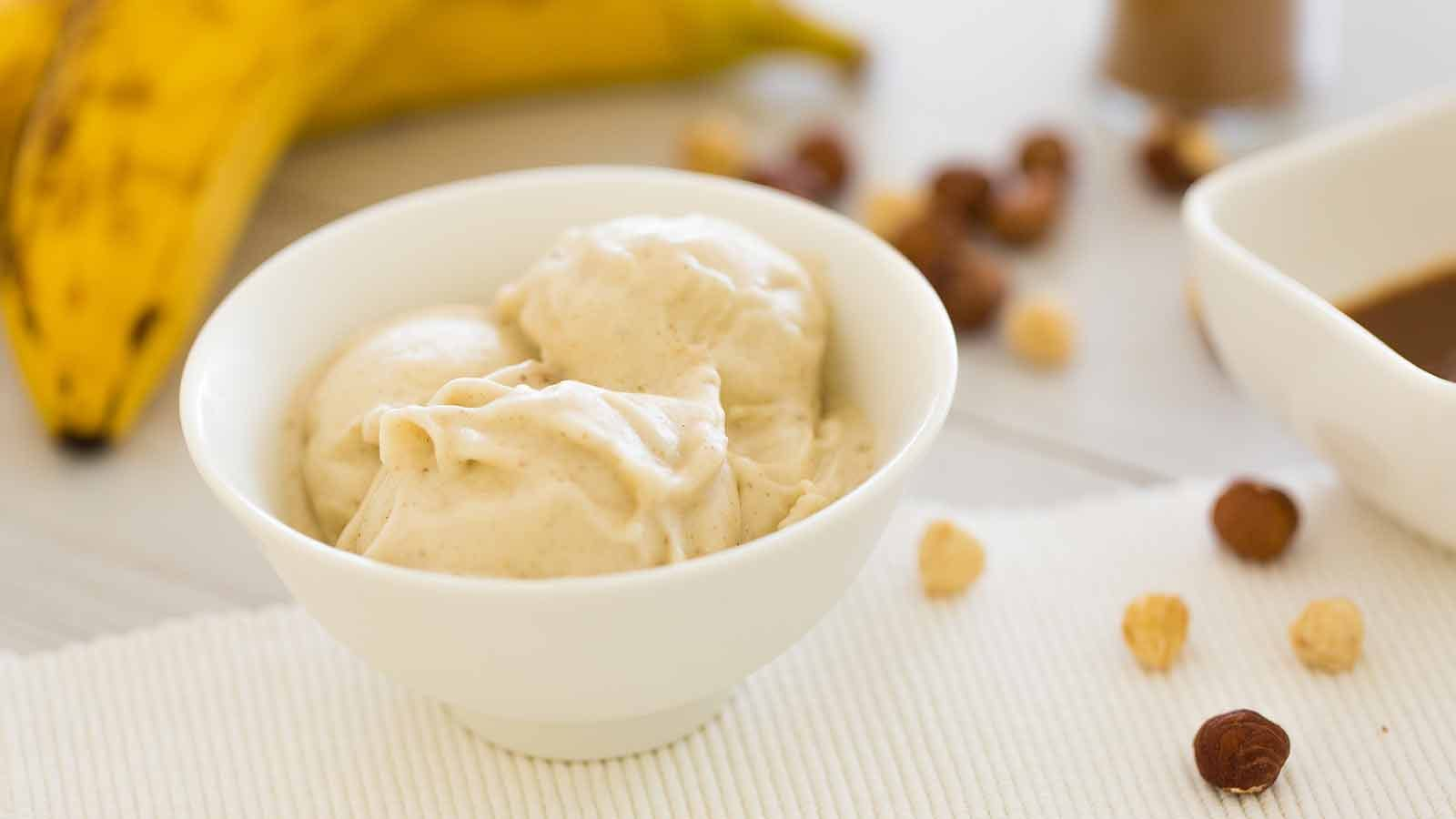A bowl of alternative ice cream sitting on a table next to some bananas, dates, and nuts.