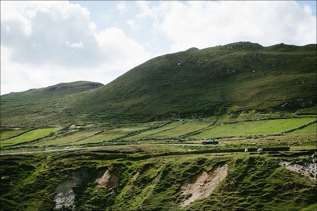 A Mustang on a road among a lush green hillside in Ireland.
