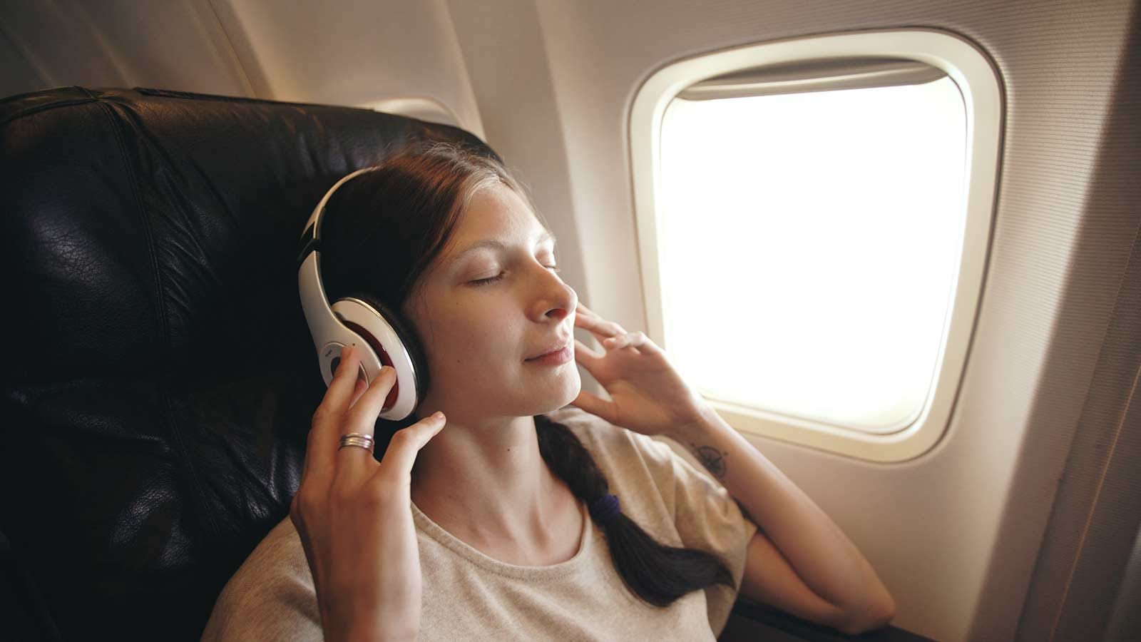 woman listening to a relaxation meditation while on an airplane