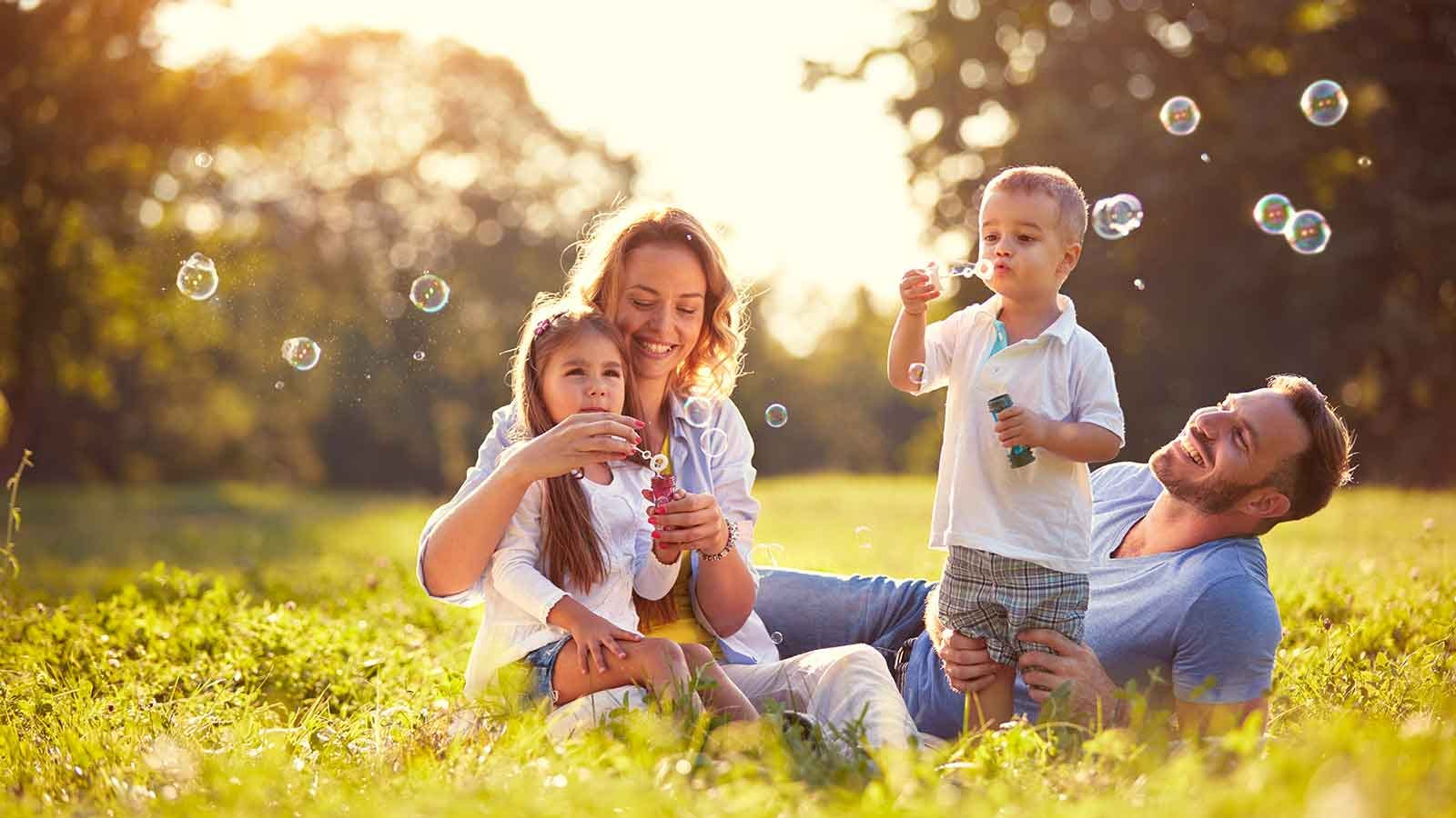 Family blowing bubbles and relaxing in a field.