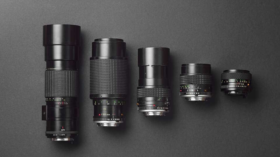 Five camera lenses of different sizes lying next to each other on a table.