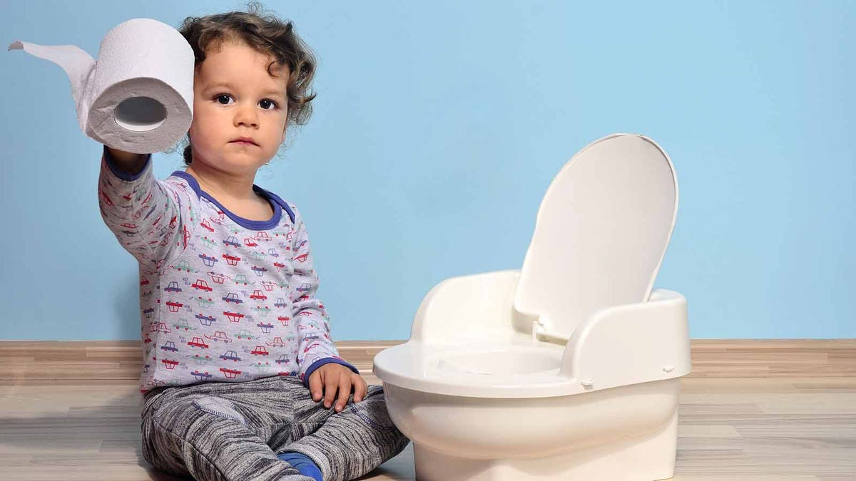 toddler sitting next to a practice potty, holding a roll of toilet paper