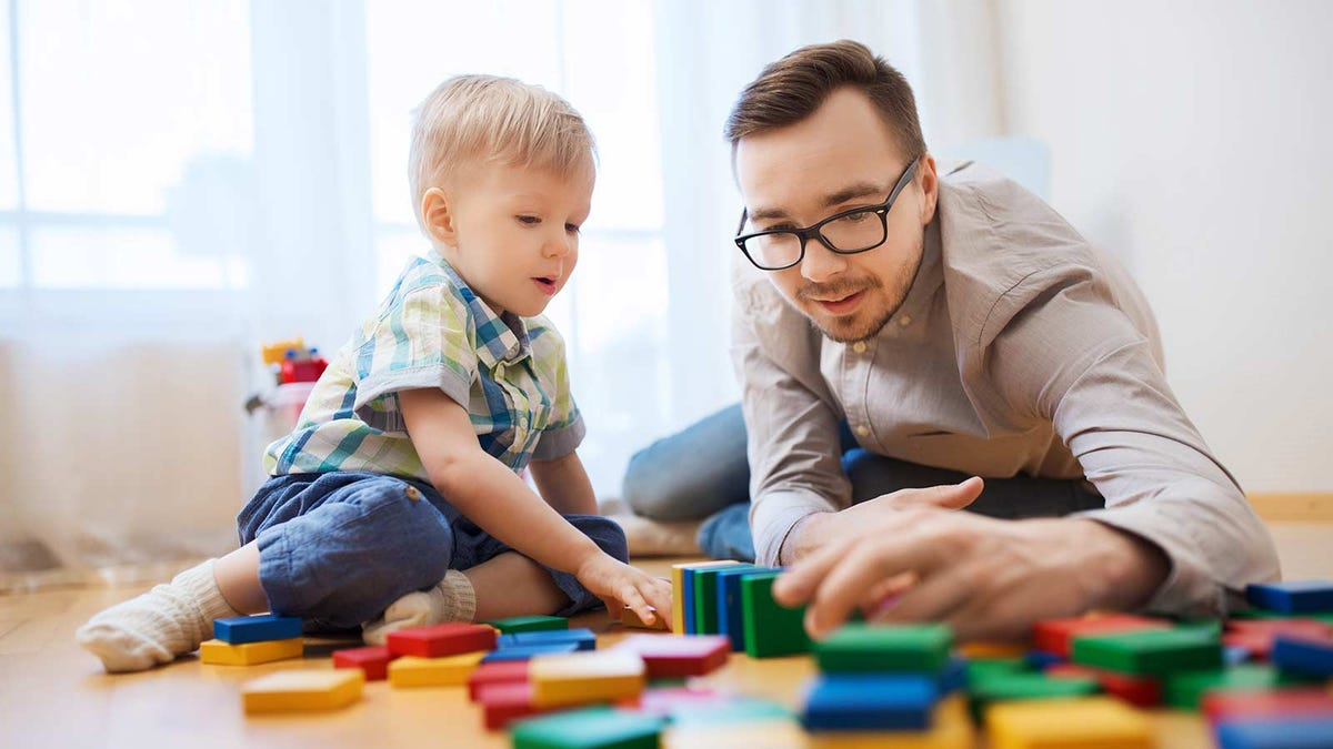 A man and a toddler playing with blocks.