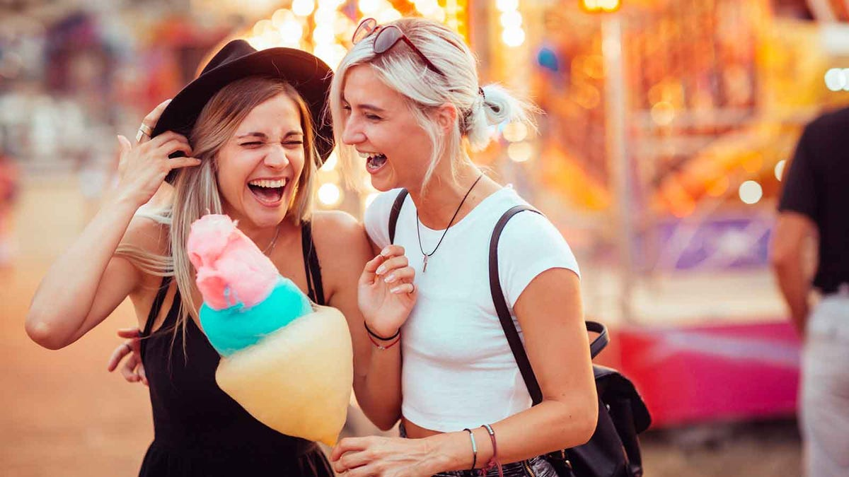 Two women laughing while eating cotton candy at a summer fair