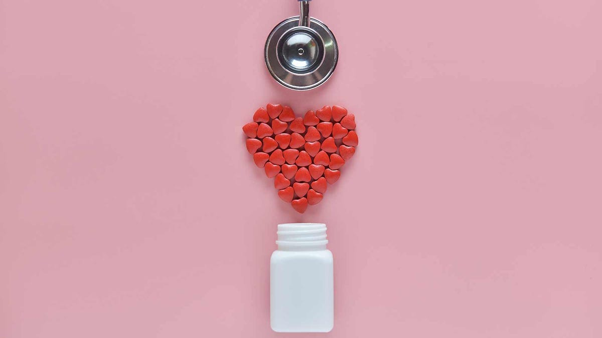 Heart shaped candies on a pink background with a stethoscope and a white medicine bottle