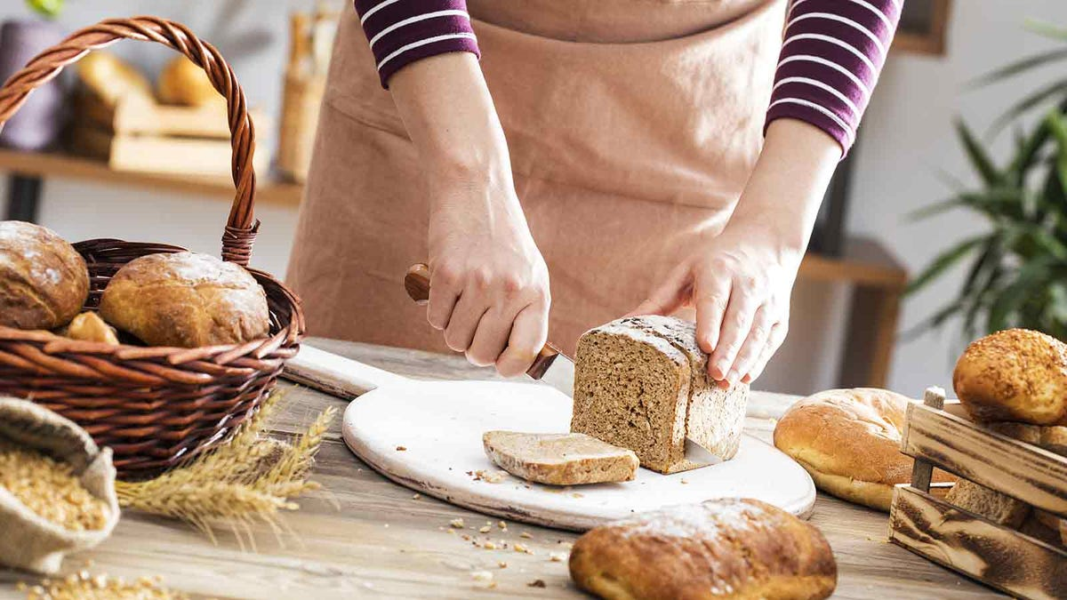 Woman's hands cutting a loaf of whole wheat bread on a cutting board.