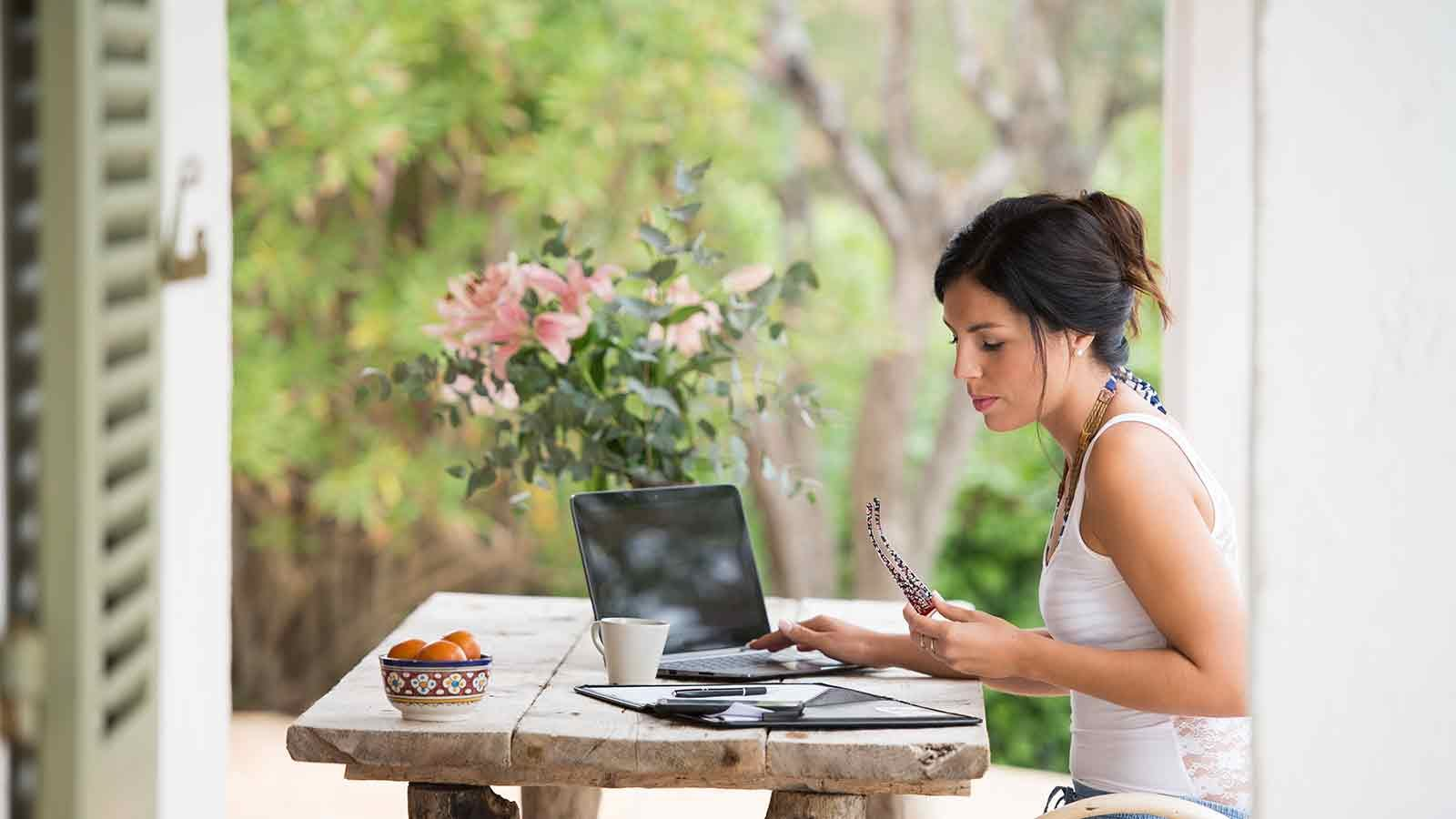 Woman sitting at a picnic table on a patio using her laptop and tablet.