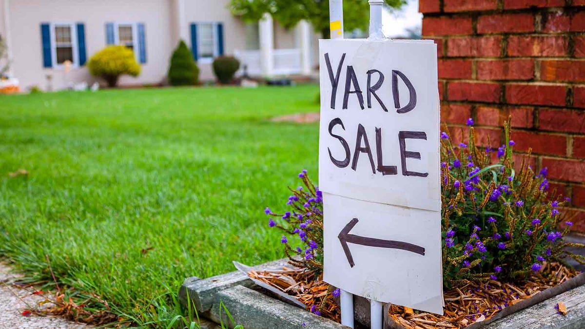 a yard sale sign in a front yard, pointing up the driveway