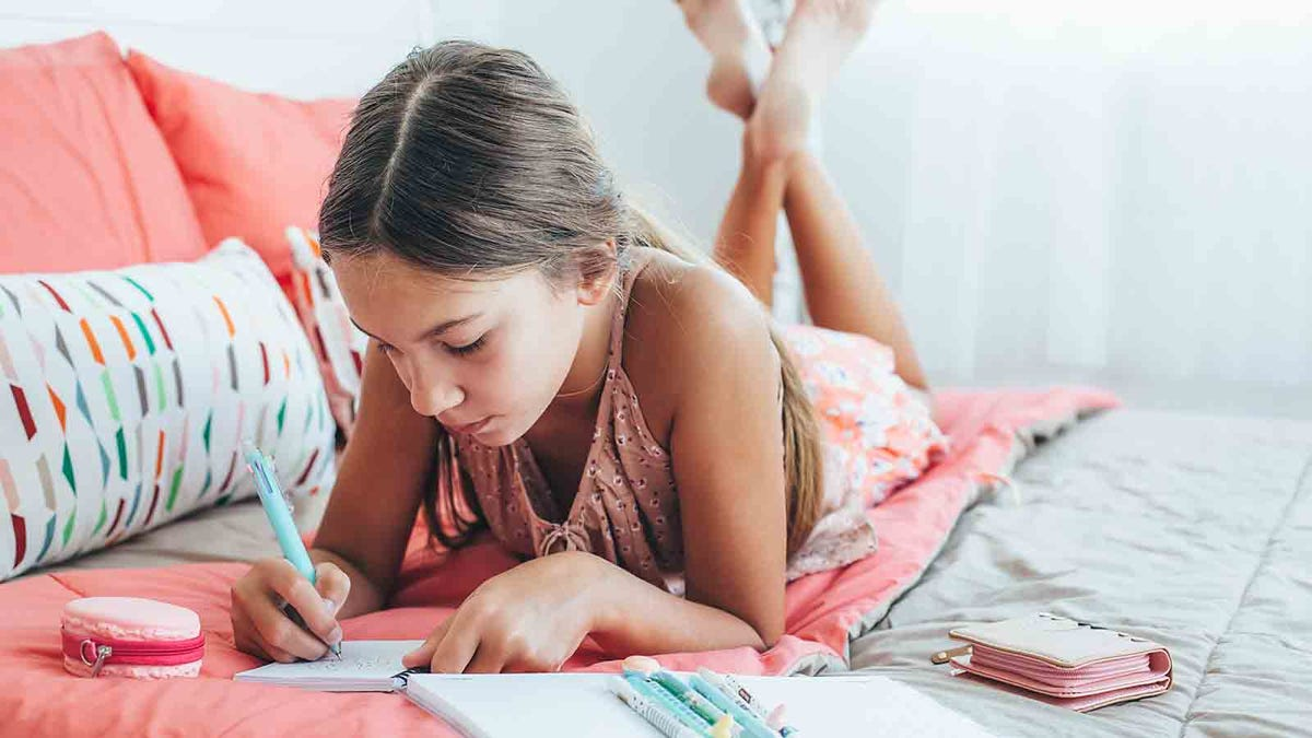 middle school age girl writing her journal on a pretty bed in a sunny bedroom