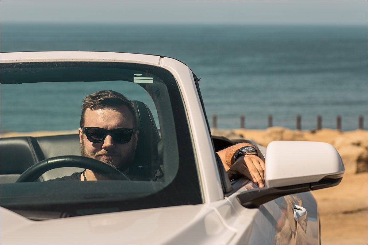 Harry Guinness sitting in a Mustang at the beach.