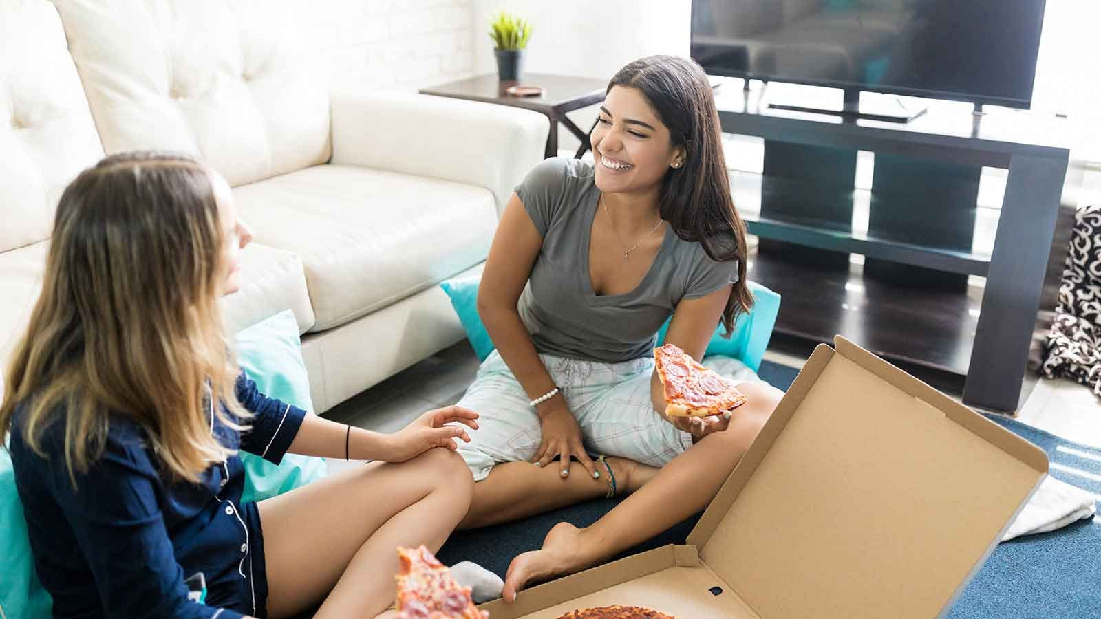 two roommates eating pizza together and laughing