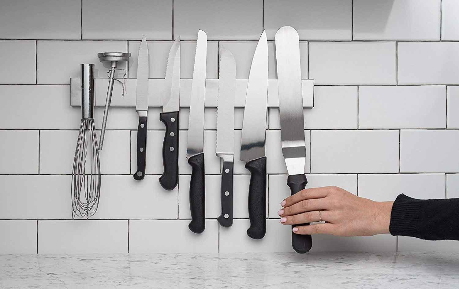 Knives and utensils hanging on a magnetic wall strip.