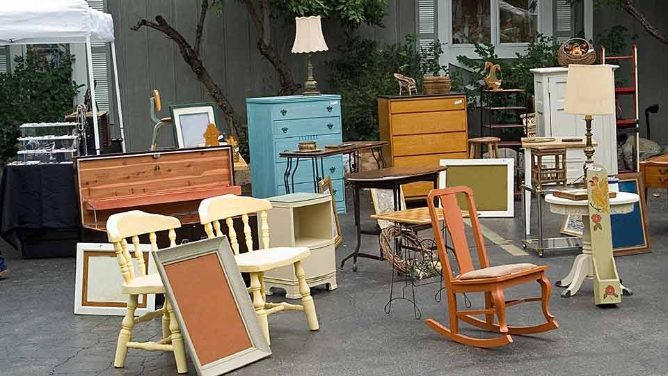furniture laid out for a garage sale, including tables, chairs, and dressers