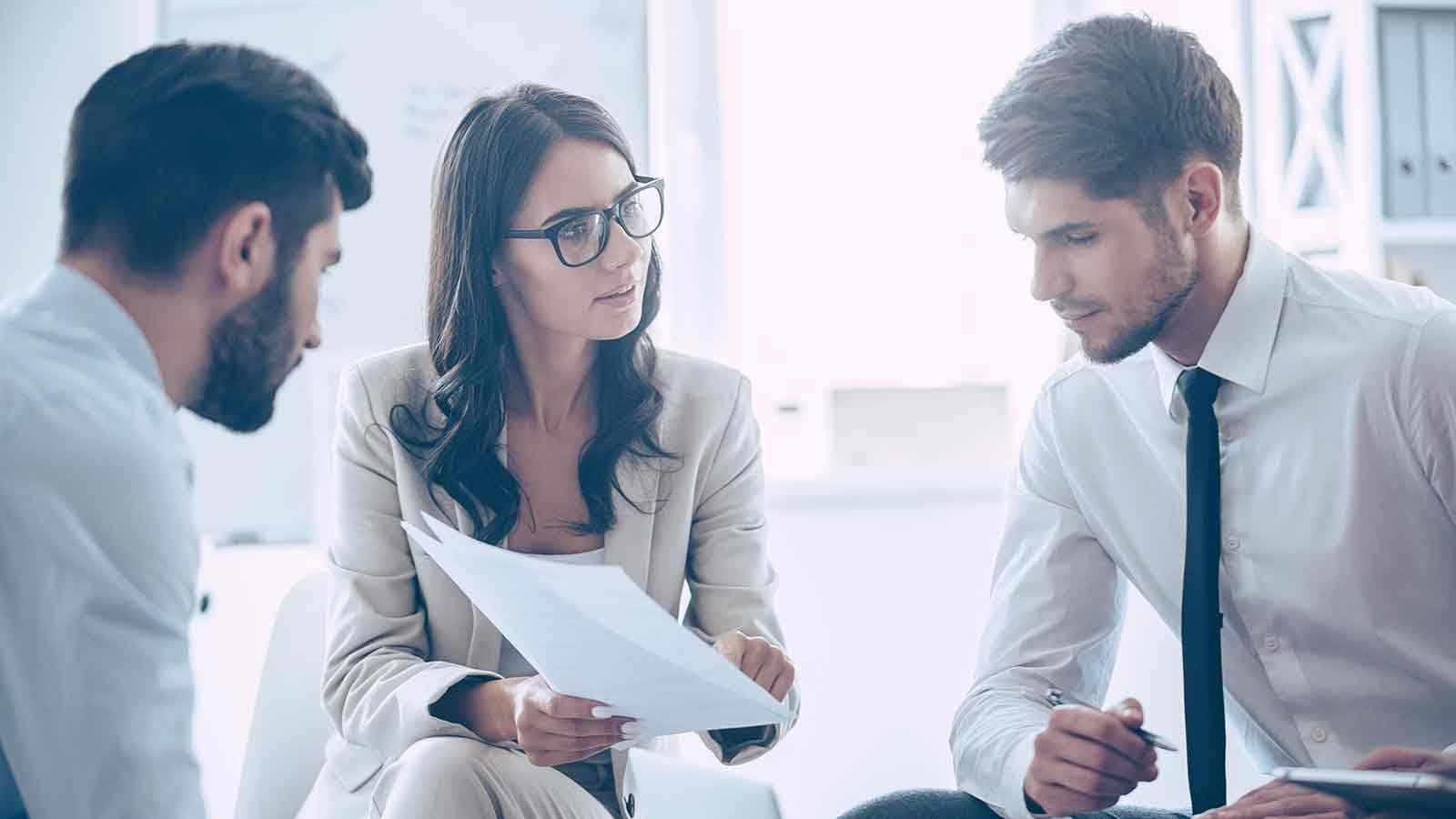 Woman discussing work documents coworkers.