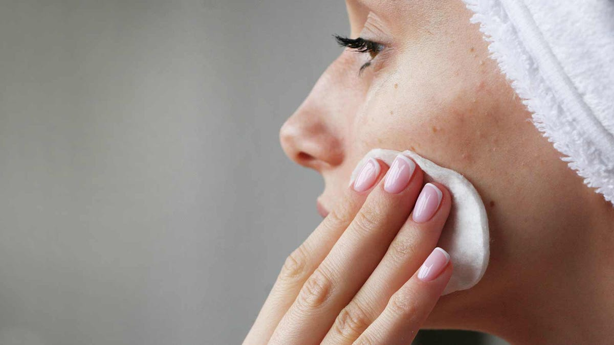 A woman cleaning her face with a makeup remover pad.