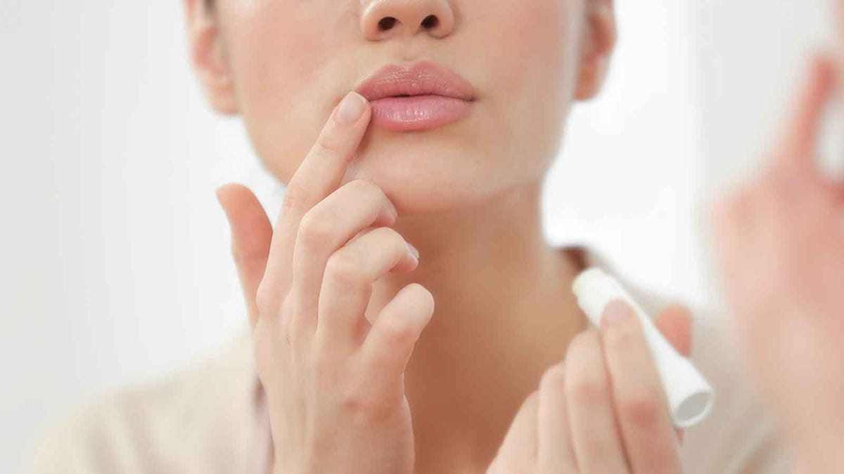 woman applying moisturizing balm to her lips