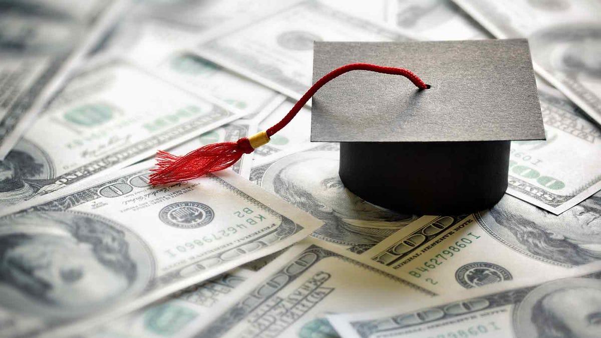a college graduation cap resting on money
