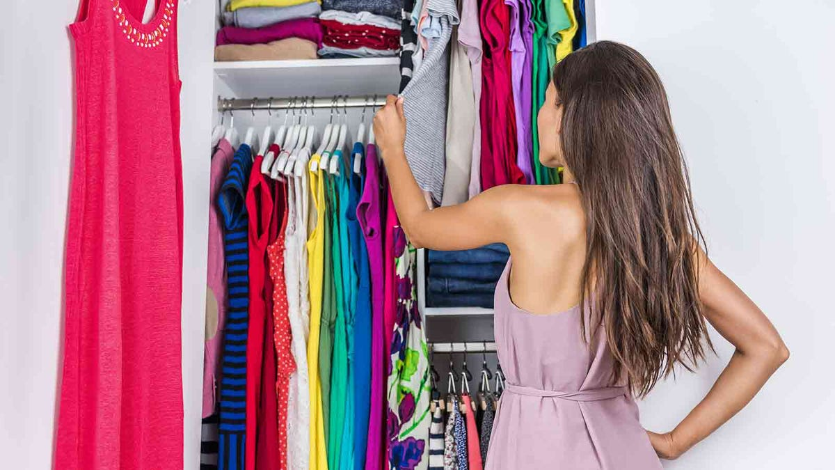 Woman looking through her closet and deciding what to purge