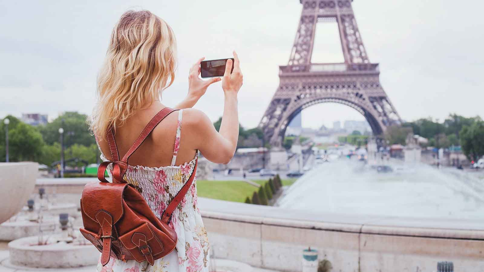 Young woman taking a picture of the Eiffel Tower with her phone.