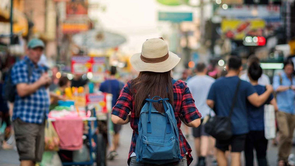 Woman wearing a backpack walking down a crowded street.