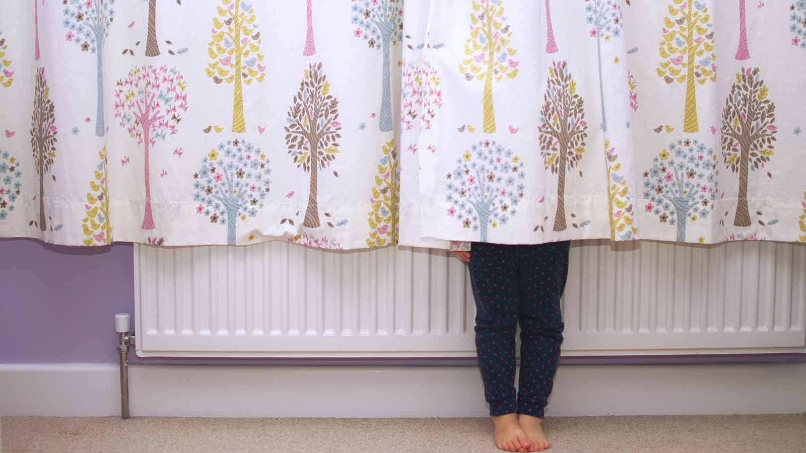 A little girl's legs showing beneath a curtain.