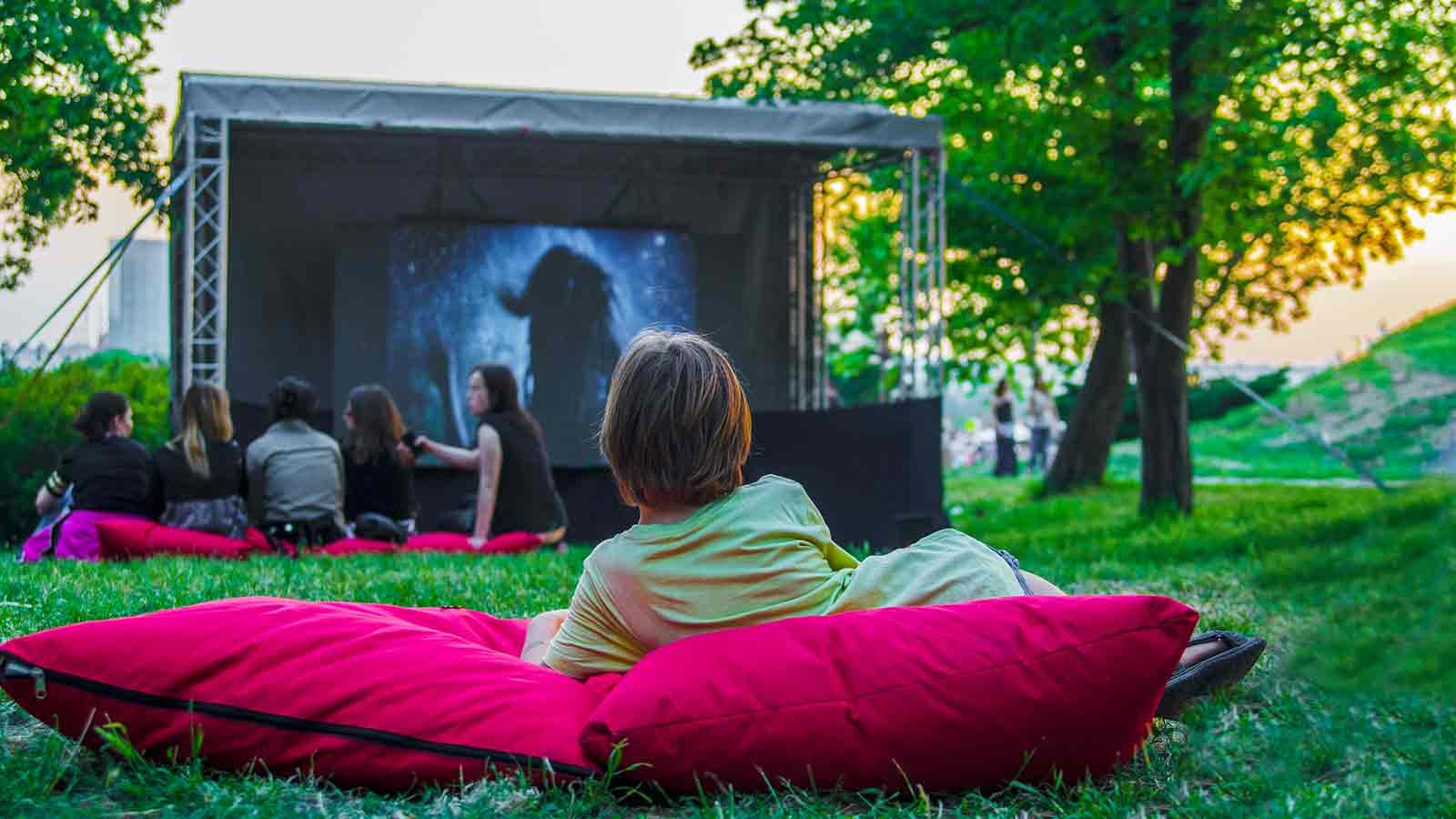 People watching a movie in a park.