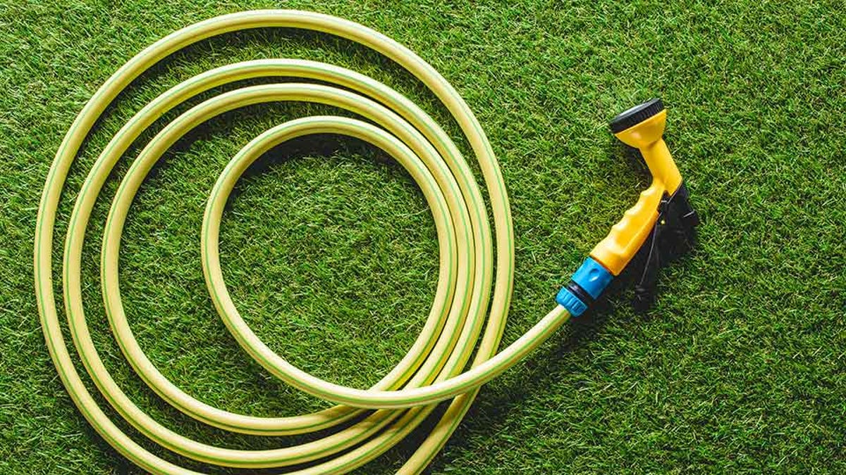 neatly coiled garden hose on a green lawn