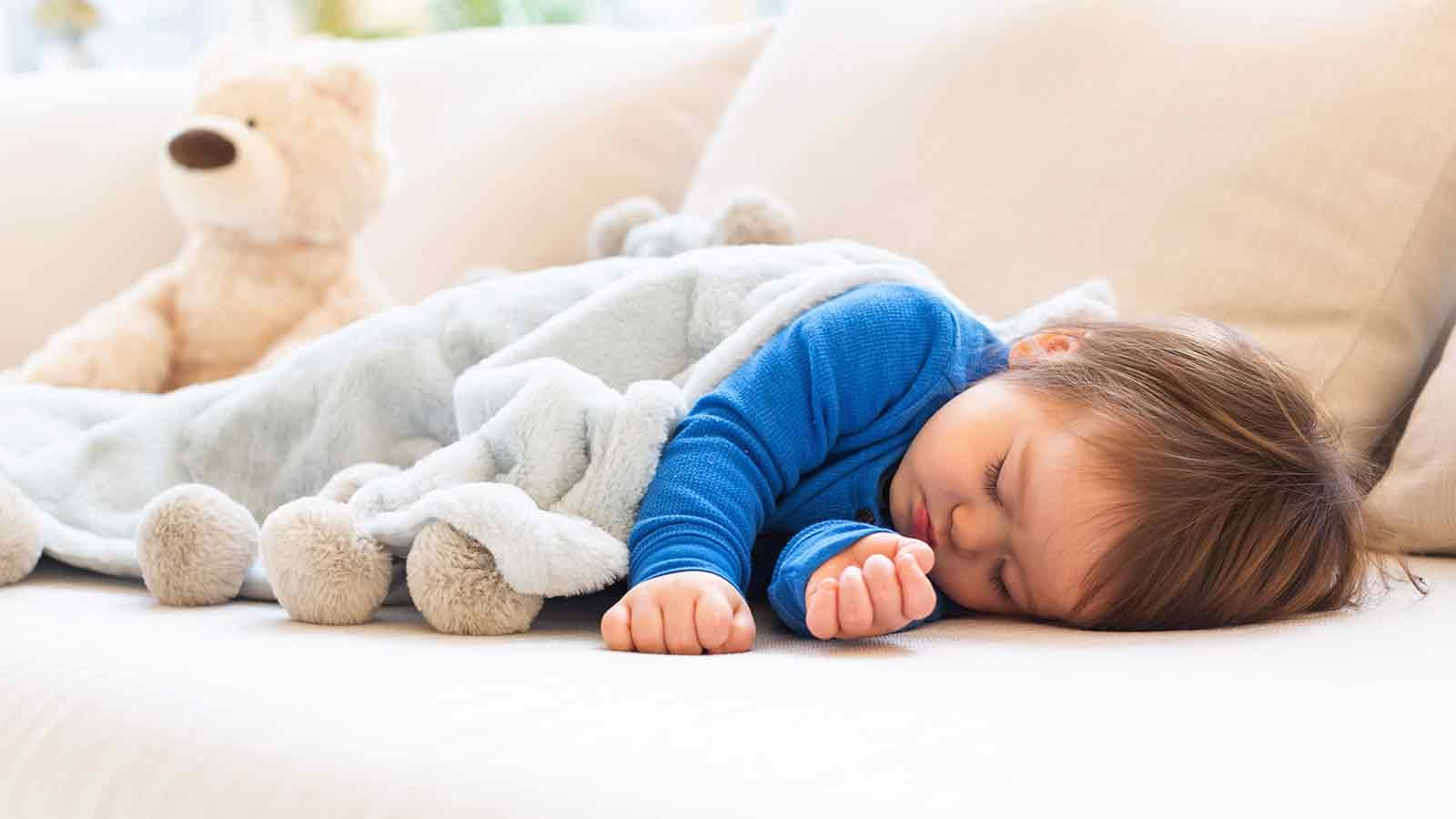 Toddler napping on a sofa.