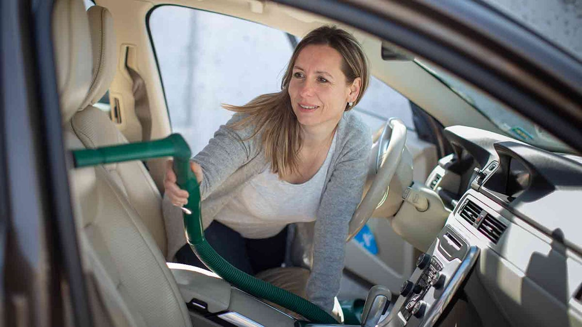 woman cleaning her car with a vacuum cleaner
