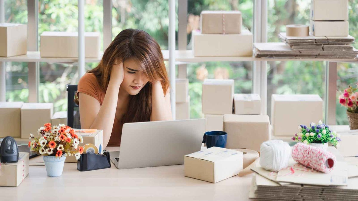 woman looking at her laptop, stressed because the work from home business turned out to be a scam