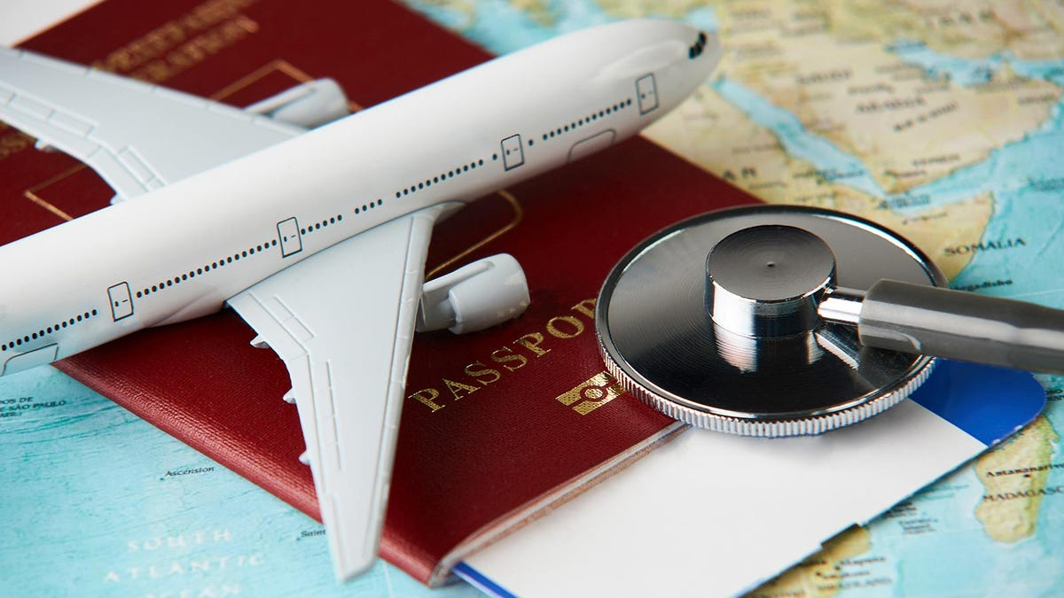 A model airplane and stethoscope rest on a passport and map.