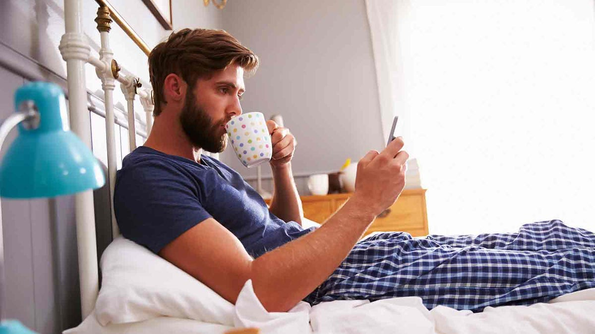 Man reading his phone in bed comfortably thanks to a long charging cable