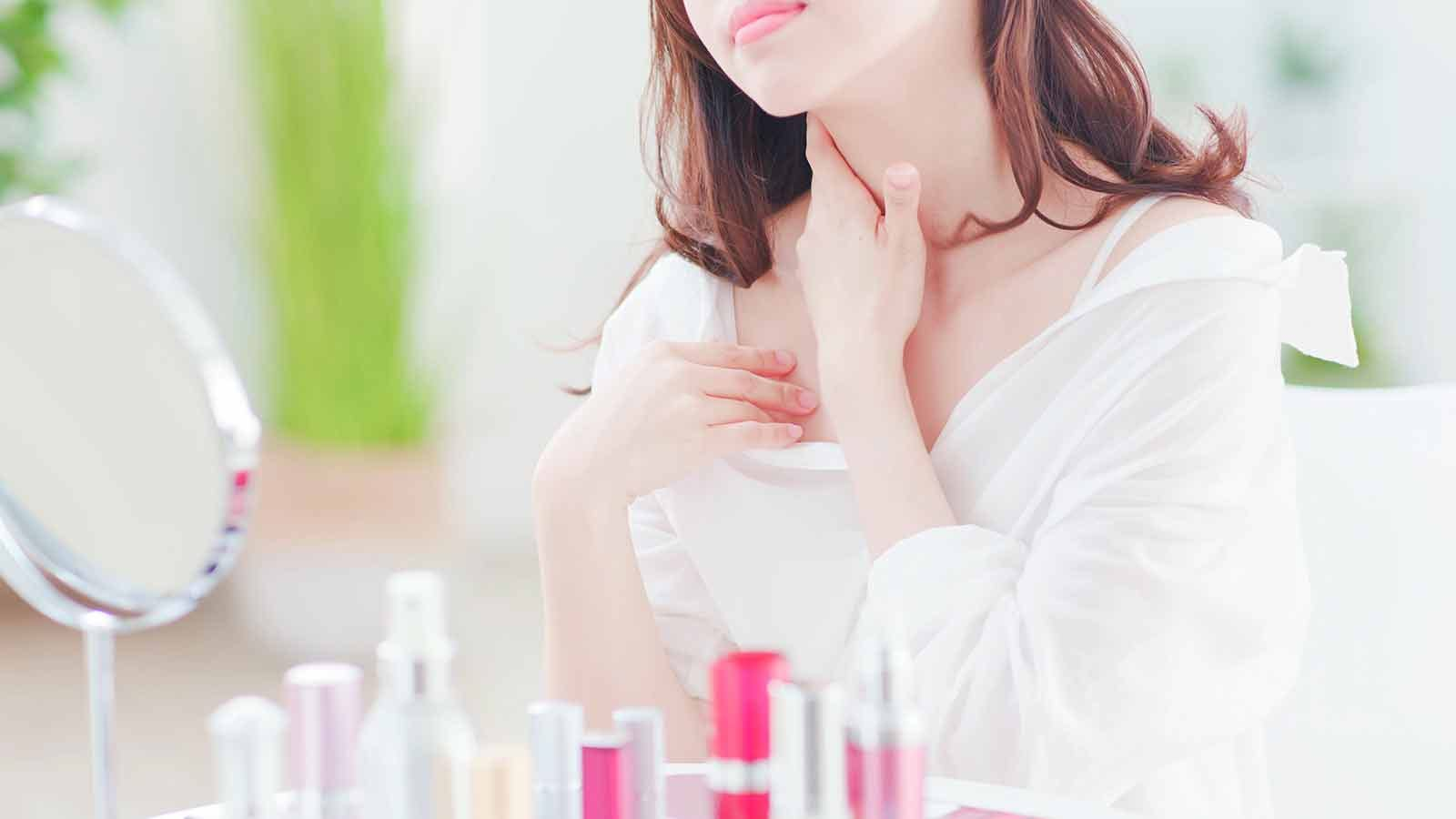 woman applying moisturizer to her neck and chest