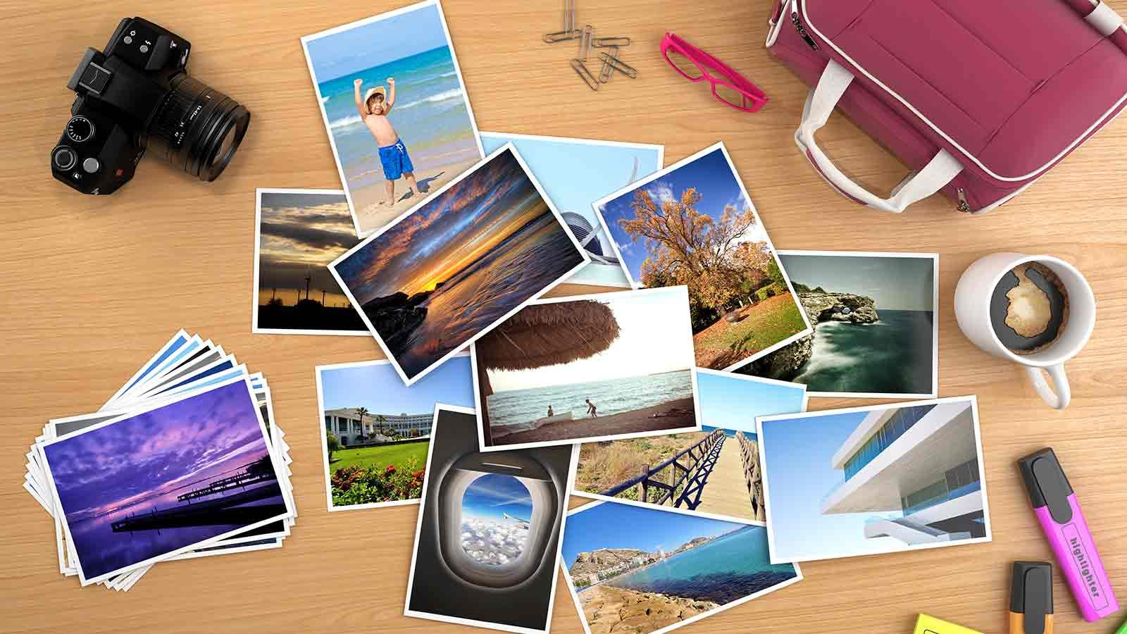 Print photos spread out on a table next to a camera.