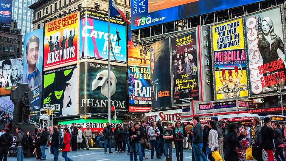Crowd in front of advertisements for Broadway plays in Times Square, New York City.