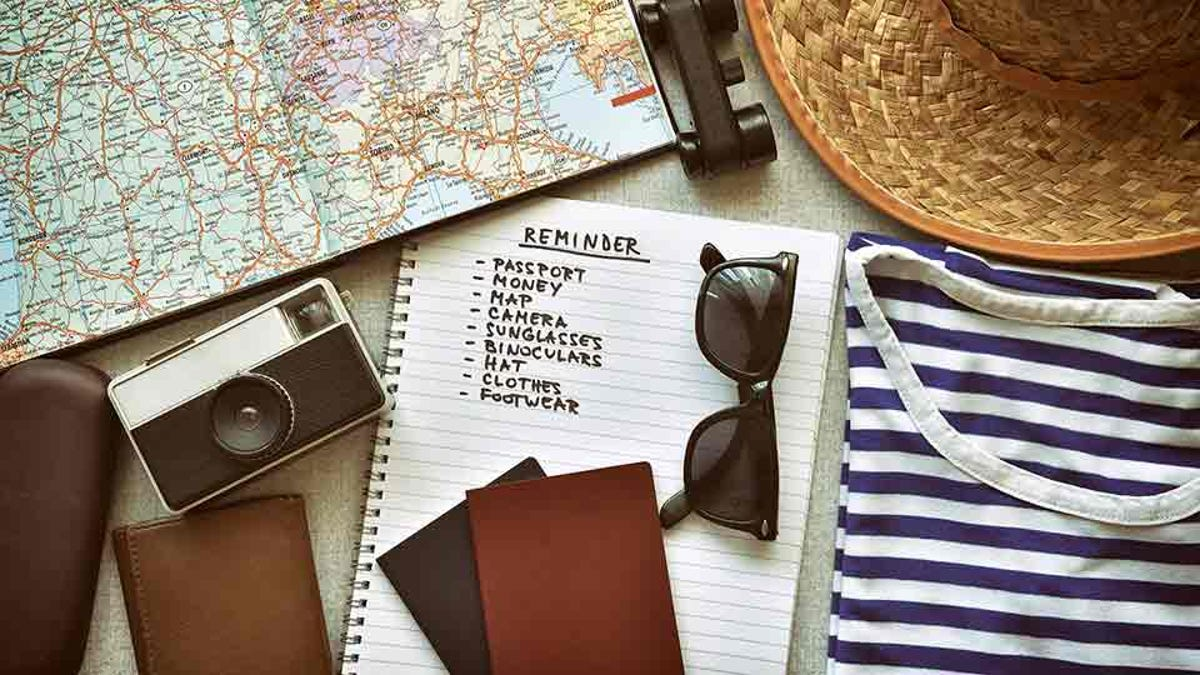 travel packing list, surrounded by travel items like a camera, sun hat, and map