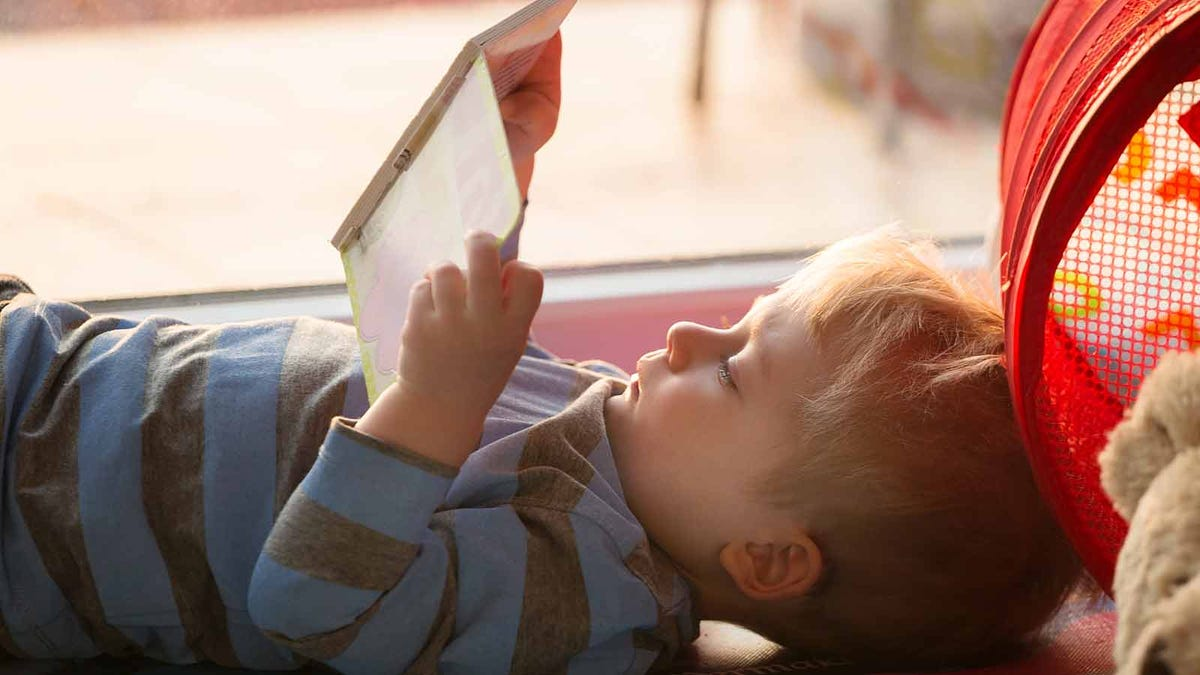 Little boy lying on his back reading a book.
