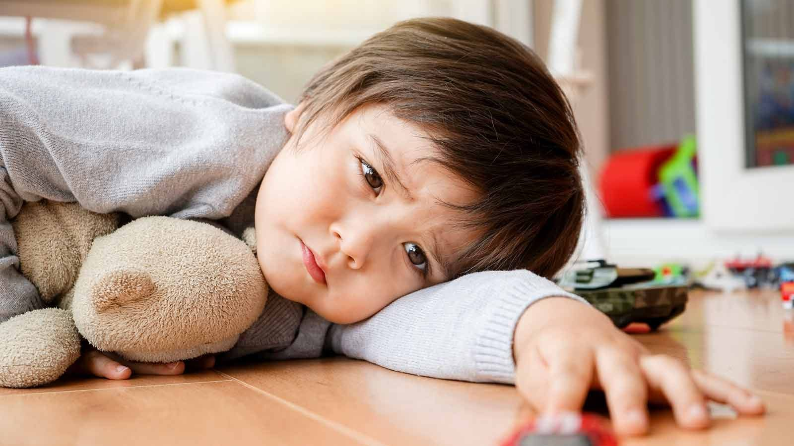 Upset toddler laying on the floor and pouting